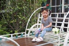 Счастливое милое капризное симпатичное прелестное lolipop игры маленькой девочки и сидит на экипаже имеет потеху внешнюю в парке  Стоковые Изображения