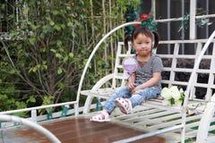 Счастливое милое капризное симпатичное прелестное lolipop игры маленькой девочки и сидит на экипаже имеет потеху внешнюю в парке  Стоковое фото RF