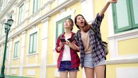 Счастливое молодое женское направление и смотреть на карте положения на smartphone сток-видео