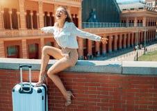 Счастливое молодое ликование женщины путешественника пока сидящ на парапете стоковые изображения rf