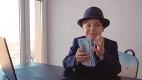 Счастливое молодое удерживание мальчика дела в стоге денег рук сидя на таблице в офисе акции видеоматериалы