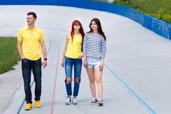 Счастливое молодые люди идя вниз с улицы и усмехаться города Стоковые Фото
