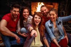 Счастливое молодые люди принимая selfie с мобильным телефоном Стоковое фото RF
