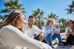 Счастливое молодые люди сидя совместно смеяться над снаружи Стоковая Фотография
