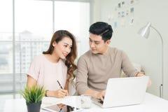 Счастливое молодые чтение пар и счеты анализировать сидя на таблице Стоковая Фотография