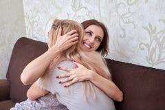 Счастливое объятие каждое другое и сидеть женщины 2 на софе в живущей комнате дома Стоковое Фото