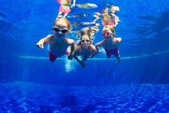 Счастливое пикирование семьи подводное в бассейне стоковое изображение rf