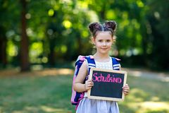 Счастливое положение девушки маленького ребенка со столом и рюкзаком или satchel Schoolkid на первый день элементарного класса r стоковые изображения rf
