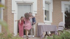 Счастливое положение семьи на крылечке совместно Мать и отец приветствовали дочь которая сыграла с друзьями около дома акции видеоматериалы
