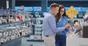 Счастливое положение человека и женщины пар семьи на счетчике с мобильными телефонами в случайных одеждах выбирая новый смартфон видеоматериал