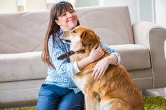 Счастливое предприниматель собаки женщины дома с золотым retriever стоковое фото