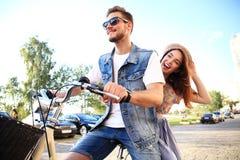 Счастливое смешное молодое катание пар на велосипеде стоковое фото