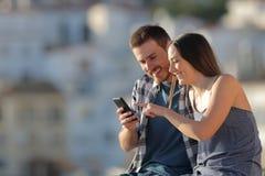Счастливое содержание сотового телефона просматривать пар в городке стоковые изображения rf