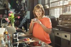 Счастливое средн-постаретое barista женщины работая на компьтер-книжке Стоковые Изображения RF