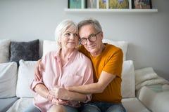 Счастливое старшее замужество обнимая совместно на кресле стоковое изображение rf