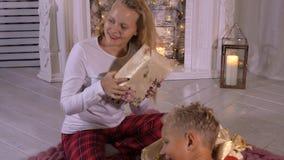 Счастливое удерживание сестры и брата в коробке подарка на рождество рук в живя комнате видеоматериал