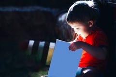 Счастливое удивленное 3 старой лет сказки книги чтения мальчика волшебной на темной предпосылке, свете приходит от книги, изолиро стоковое фото