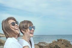 2 счастливое, усмехаясь девушки на пляже Ощущение утехи между 2 друзьями Стоковое Изображение RF