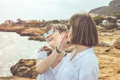 2 счастливое, усмехаясь девушки на пляже Социальная фотография стиля сети Стоковые Изображения