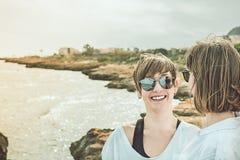 2 счастливое, усмехаясь девушки на пляже Социальная фотография стиля сети Стоковые Фото