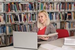 Счастливое чтение студентки от книги в библиотеке Стоковое Изображение RF