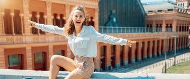 Счастливое элегантное туристское ликование женщины пока сидящ на парапете стоковые изображения