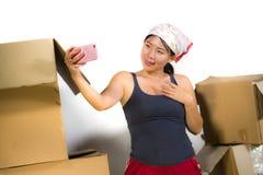 Счастливой азиатской корейской возбужденный женщиной дома пол живя комнаты распаковывая пожитки от картонных коробок двигая к нов стоковые фотографии rf
