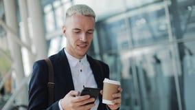 Счастливо усмехаясь привлекательный человек идя вниз по улице и используя смартфон Он выпивая кофе, который нужно пойти и чтение  видеоматериал