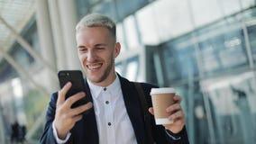 Счастливо усмехаясь привлекательный человек идя вниз по улице и используя смартфон Он выпивая кофе, который нужно пойти и чтение  сток-видео