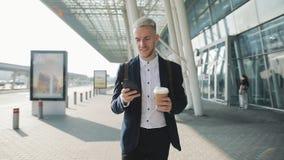 Счастливо усмехаясь привлекательный человек идя вниз по улице и используя смартфон Он выпивая кофе, который нужно пойти Крупный а видеоматериал
