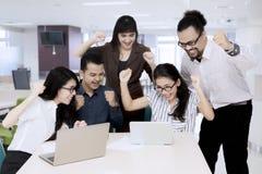Счастливые азиатские бизнесмены смотря портативный компьютер Стоковые Изображения