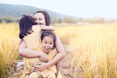 Счастливые азиатские девушки маленького ребенка обнимая мать Стоковые Фотографии RF
