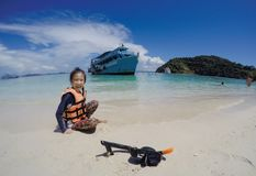 Счастливые азиатские спасательный жилет, маска и шноркель носки девушки, наслаждаются сыграть песок на пляже, достопримечательнос стоковое фото