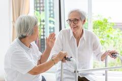 Счастливые 2 азиатских старших друз женщин держа руки для заботы, поддержки и потехи говоря, времени совместно, старые люди усмех стоковое изображение