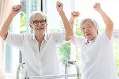 Счастливые 2 азиатских старших женщины поднимая кулак и hurrah, время совместно, друзей пожилых женщины или сестры усмехаясь, сме стоковые фото