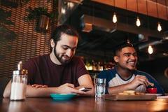 Счастливые аравийские молодые человеки вися в кафе просторной квартиры 2 друз смешанных гонки имея потеху в Лаунж-баре Стоковое фото RF