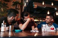 Счастливые аравийские молодые человеки вися в кафе просторной квартиры Группа в составе люди смешанной гонки имея потеху в Лаунж- стоковое фото