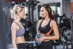 счастливые атлетические женщины в современном sportswear говоря друг к другу Стоковая Фотография