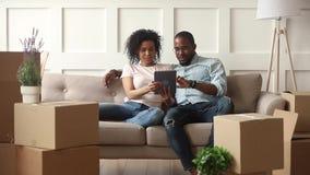 Счастливые африканские пары используют цифровой планшет на двигая день сток-видео