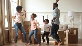 Счастливые африканские родители и дети семьи танцуя празднующ двигая день сток-видео