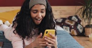 Счастливые Афро-американские беседовать и обмен текстовыми сообщениями девушки на смартфоне лежа на кровати дома Молодая женщина  сток-видео