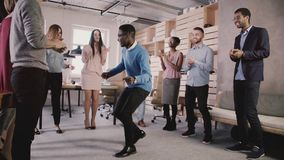 Счастливые Афро-американские танцы босса с работниками на партии офиса teambuilding, празднуя замедленное движение успеха команды видеоматериал