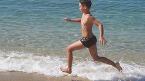 Счастливые бега ребенка вдоль пляжа на заходе солнца движение медленное акции видеоматериалы