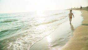 Счастливые бег и скачка мальчика весело и брызгающ в морской воде в заходе солнца Slowmo видеоматериал