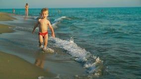 Счастливые бег и скачка мальчика весело и брызгающ в морской воде в заходе солнца Slowmo акции видеоматериалы