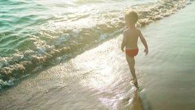 Счастливые бег и скачка мальчика весело и брызгающ в морской воде в заходе солнца Slowmo сток-видео