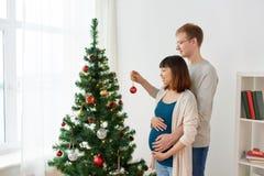 Счастливые беременные жена и супруг на рождественской елке Стоковые Изображения