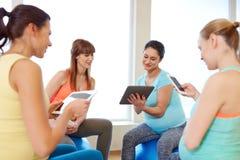 Счастливые беременные женщины с ПК таблетки в спортзале Стоковые Изображения RF