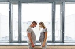 Счастливые беременные молодые пары стоя совместно на окне Будущий отец имеет бак-живот Стоковое Изображение
