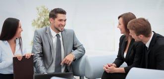 Счастливые бизнесмены говоря на встрече на офисе Стоковая Фотография